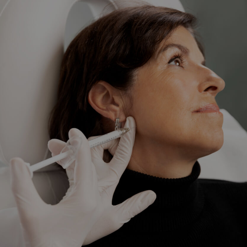 A female patient at Clinique Chloé receiving dermal filler injections in their jaw for jawline definition