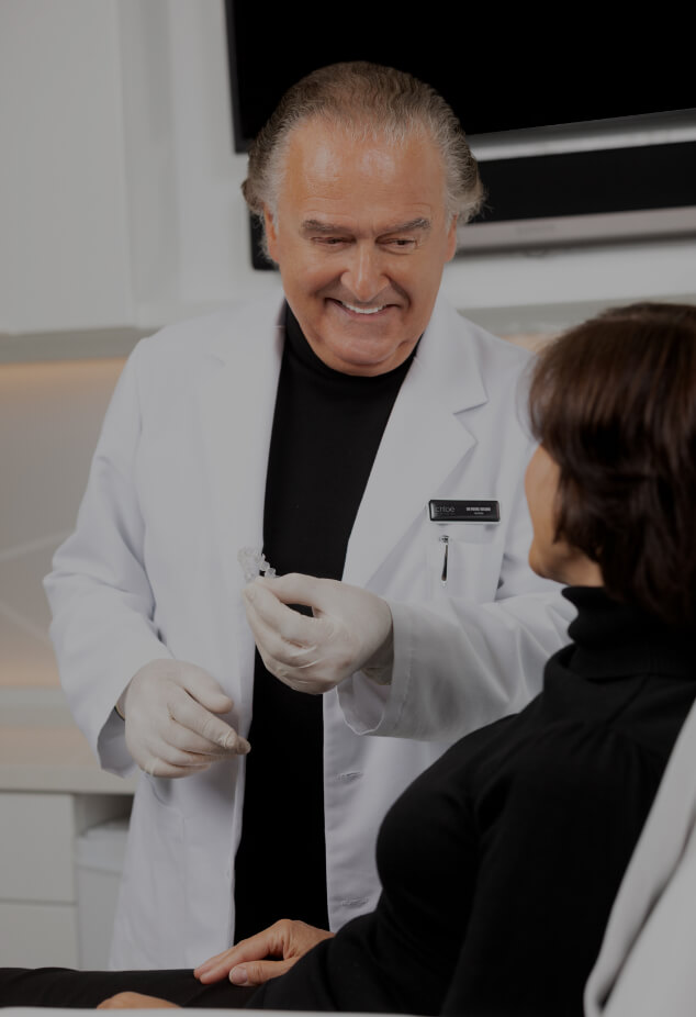 Dr. Pierre Rochon, dentist, explaining and demonstrating to his patient how to use Invisalign aligners