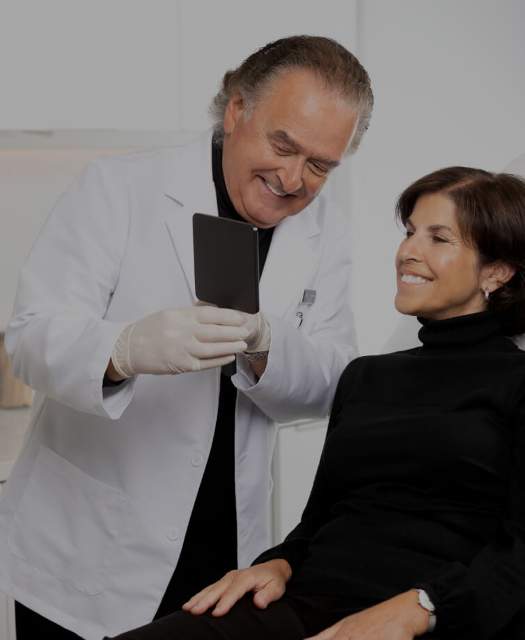 Dr. Pierre Rochon, dentist, holding a mirror in his hand so that his patient sitting next to him can see her smile