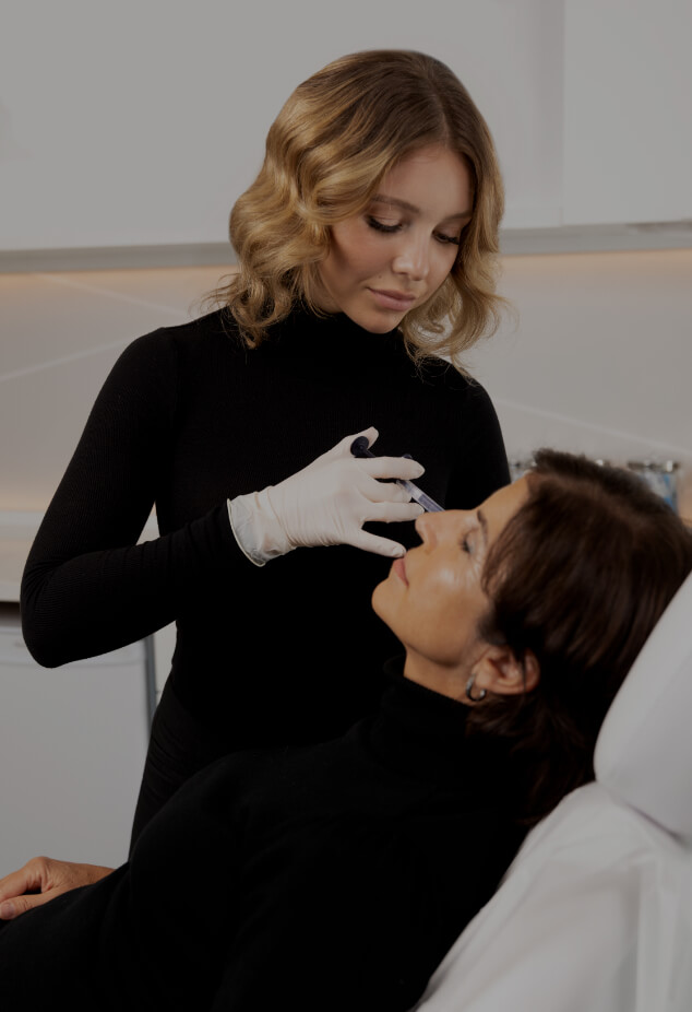 Nurse injector Amélie Castonguay performing dermal filler injections on the cheeks of a female patient