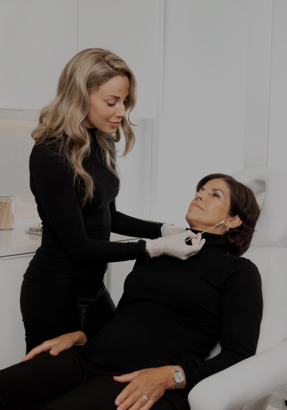 Nurse injector Anabel St-Onge preparing a dermal filler syringe in front of a female patient before her treatment