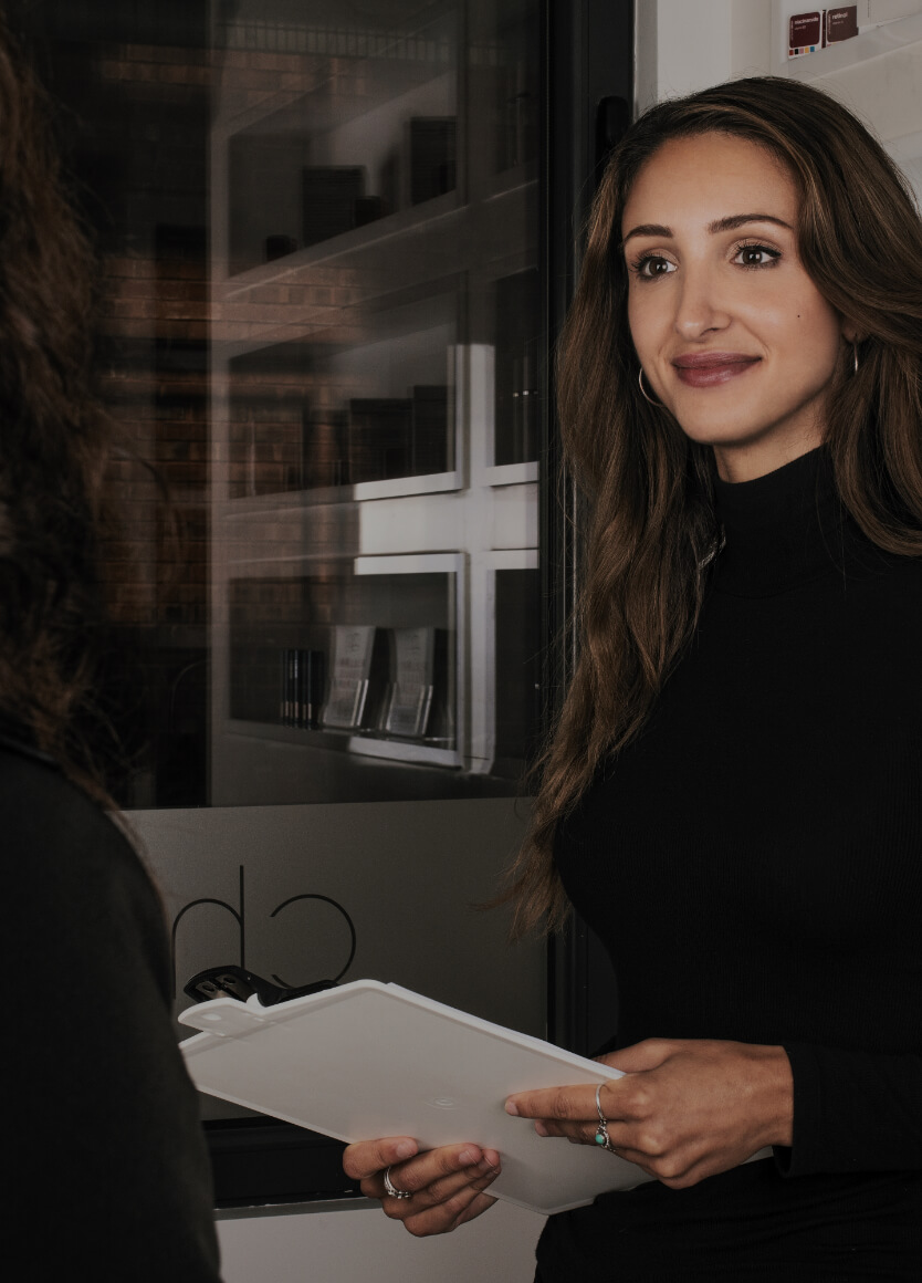 Medical receptionist Alexia D'Antico welcoming a patient at Clinique Chloé with a medical questionnaire in hand
