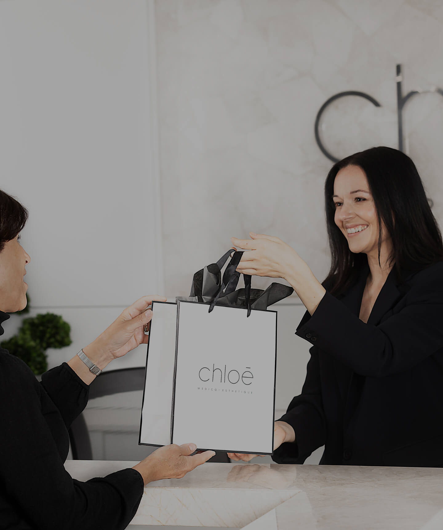 Medical receptionist Guylaine Lavoie giving a Clinique Chloé gift bag to a patient