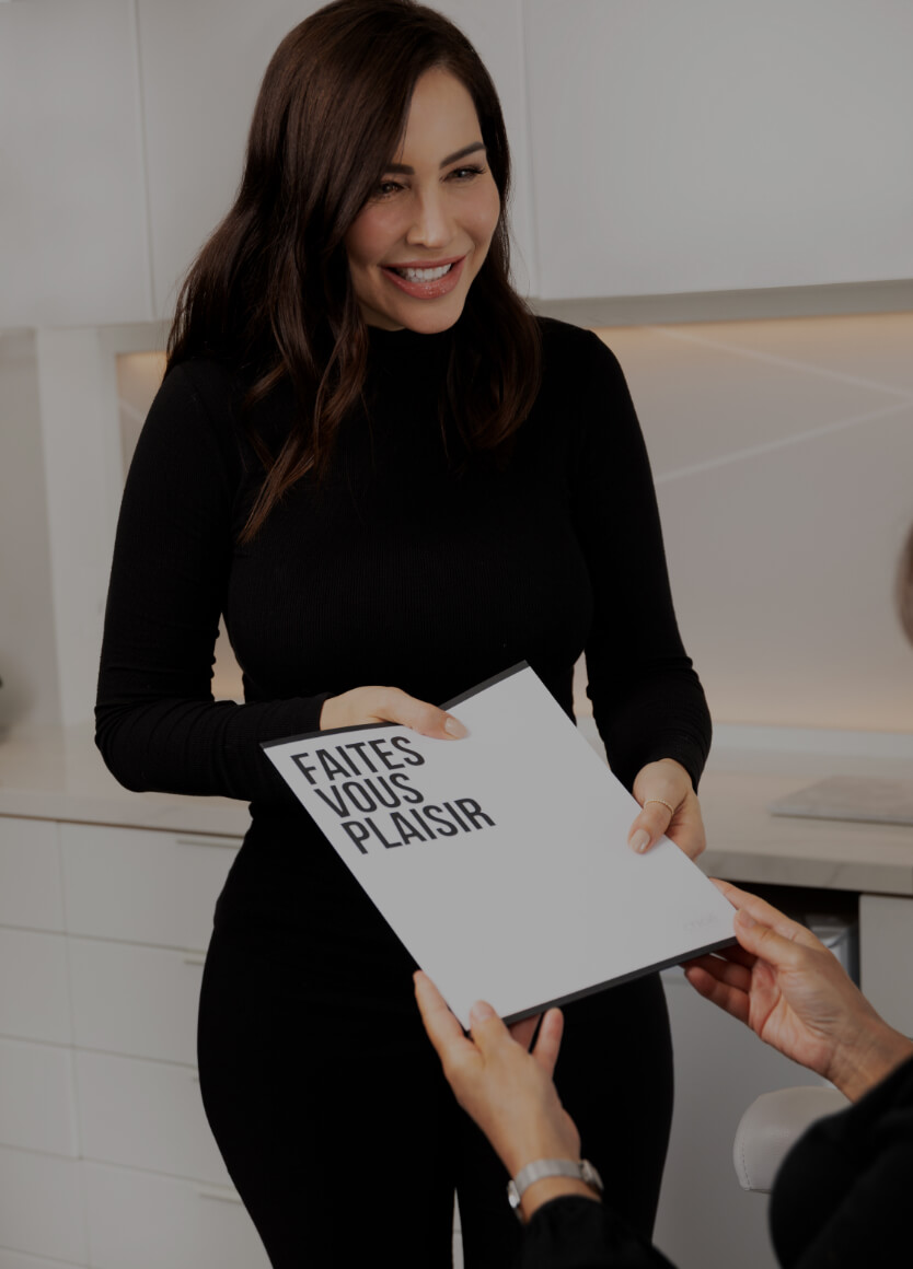 The medico-aesthetic technician Nadia Jobin giving a treatment plan to her patient in a Clinique Chloé folder