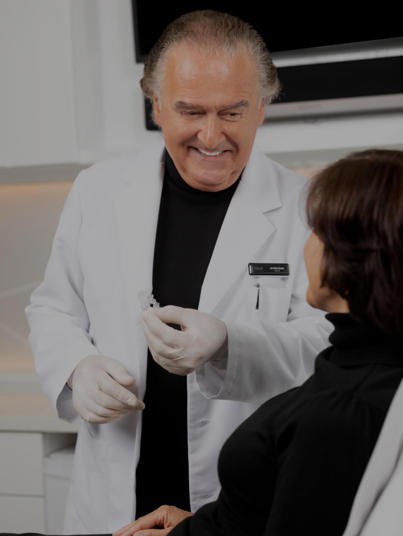 Dr Pierre Rochon, dentiste, expliquant et démontrant à sa patiente comment employer les aligneurs Invisalign
