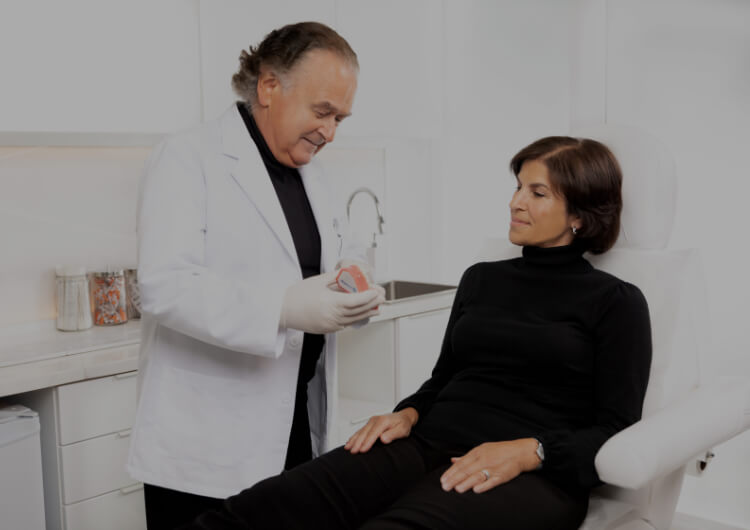 Dr Pierre Rochon, dentiste, tenant un miroir dans sa main afin que sa patiente assise à ses côtés puisse voir son sourire