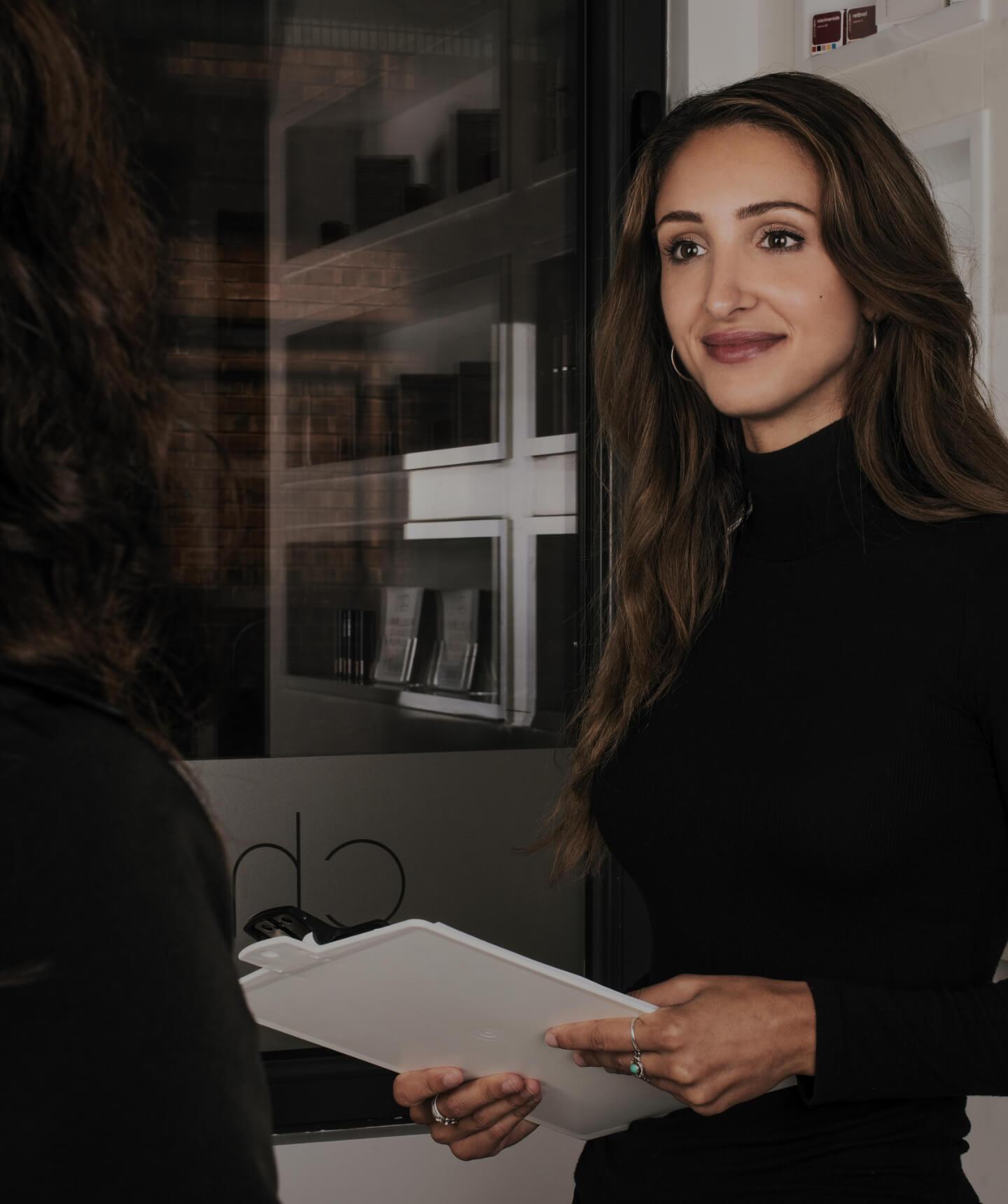 La réceptionniste médicale Alexia D'Antico accueillant une patiente de la Clinique Chloé avec un questionnaire médical en main
