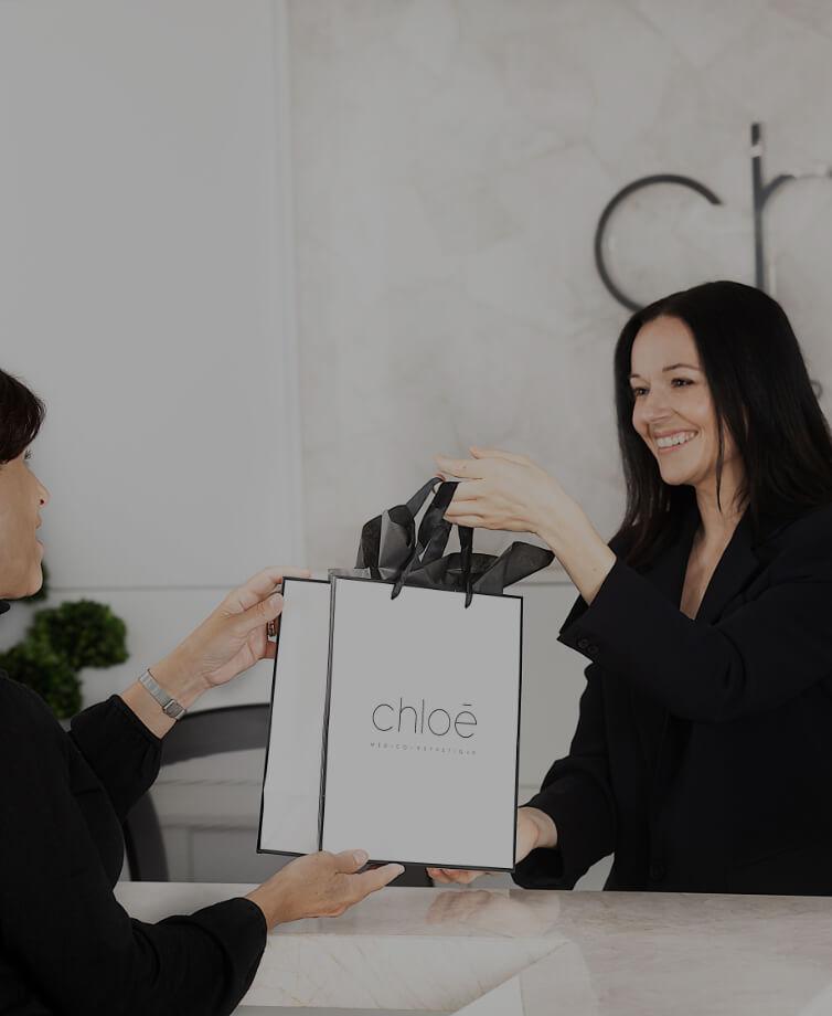 La réceptionniste médicale Guylaine Lavoie remettant un sac cadeau de la Clinique Chloé à une patiente