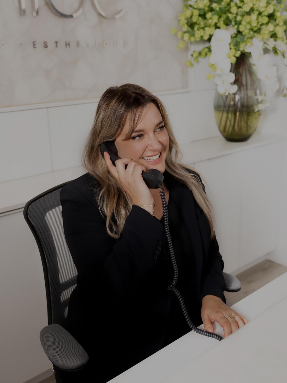 La réceptionniste médicale Karine Leduc assise à la réception de la Clinique Chloé au téléphone avec un patient