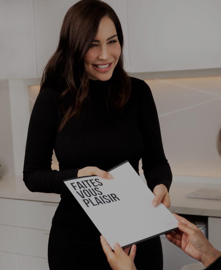 La technicienne médico-esthétique Nadia Jobin remettant un plan de traitement dans un porte-document à sa patiente