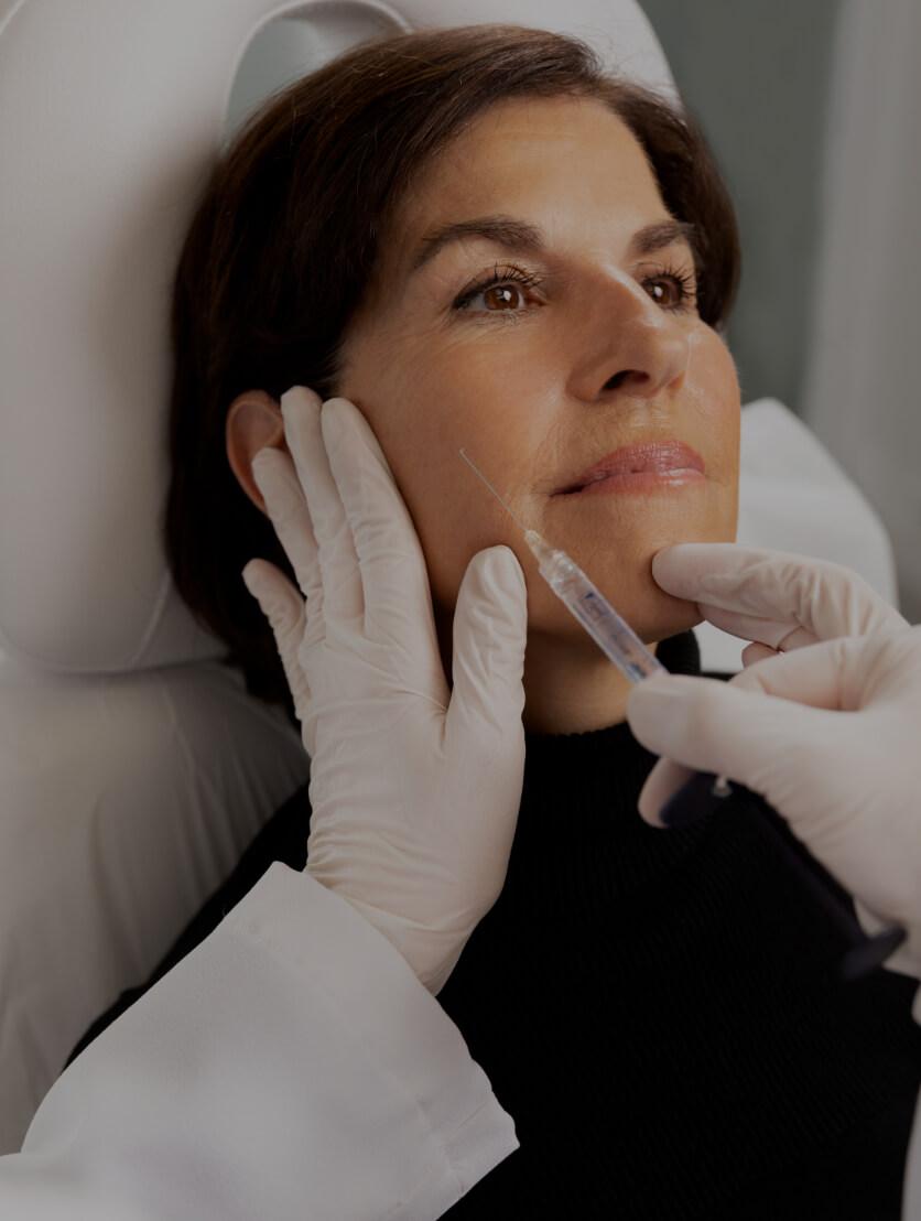Dre Chloé Sylvestre effectuant des injections d'agents de comblement dans les pommettes d'une patiente