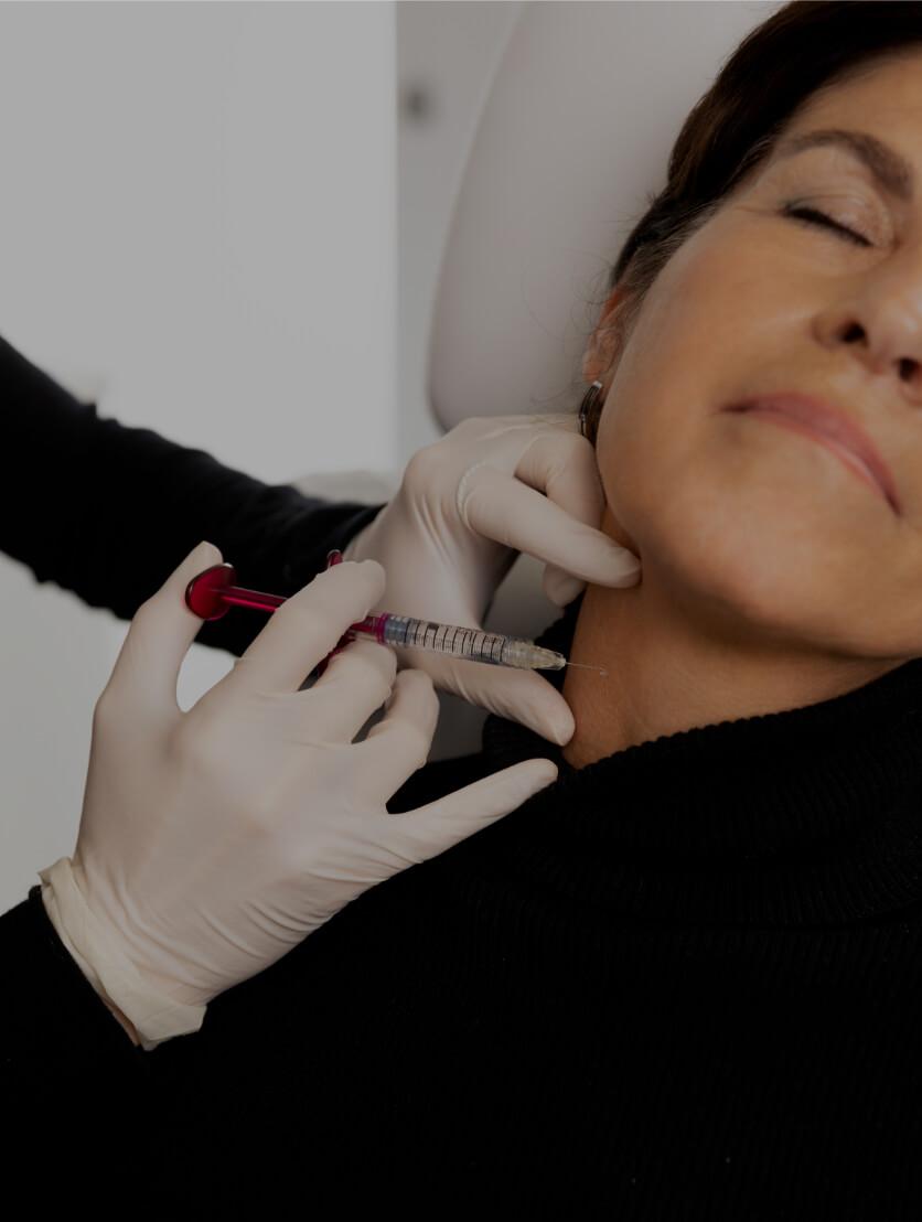 Un médecin de la Clinique Chloé effectuant un traitement de mésothérapie dans le cou d'une patiente