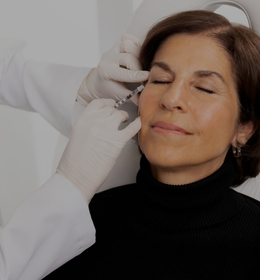 Un médecin de la Clinique Chloé traitant les pattes d'oie d'une patiente avec des injections de neuromodulateurs