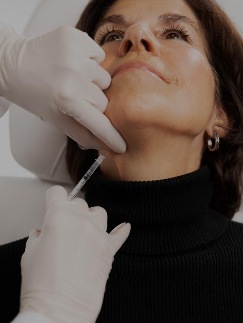Un médecin de la Clinique Chloé traitant les cordes platysmales d'une patiente avec des injections de neuromodulateurs