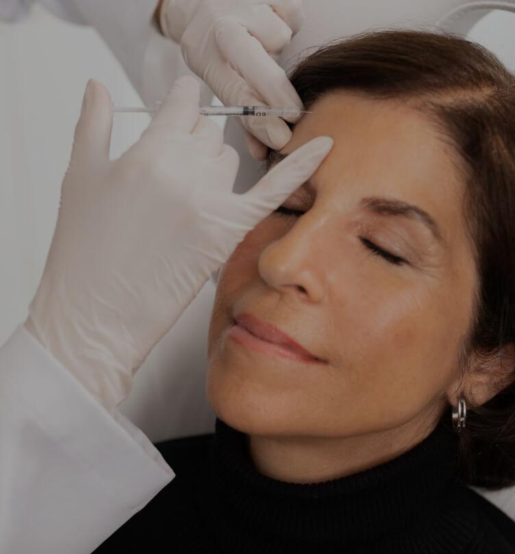 Un médecin de la Clinique Chloé effectuant des injections de neuromodulateurs dans le front d'une patiente