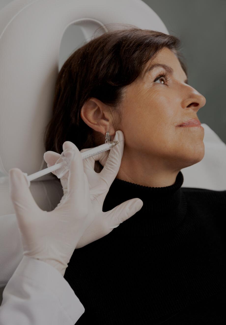 Un médecin de la Clinique Chloé pratiquant des injections de Radiesse dans la ligne de la mâchoire d'une patiente