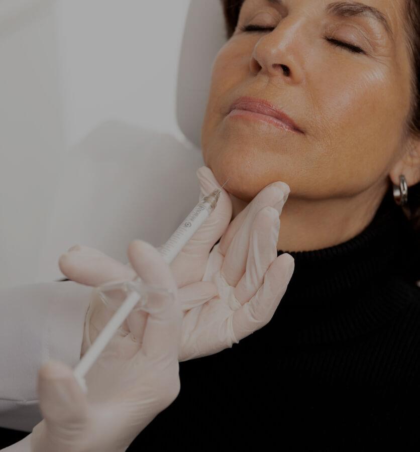 Un médecin de la Clinique Chloé pratiquant des injections de Radiesse dans le menton d'une patiente