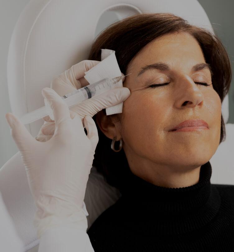 Un médecin de la Clinique Chloé effectuant des injections de Sculptra dans les tempes d'une patiente