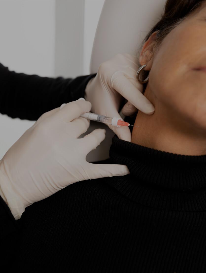 Un médecin de la Clinique Chloé pratiquant des injections de Skinboosters dans le cou d'une patiente