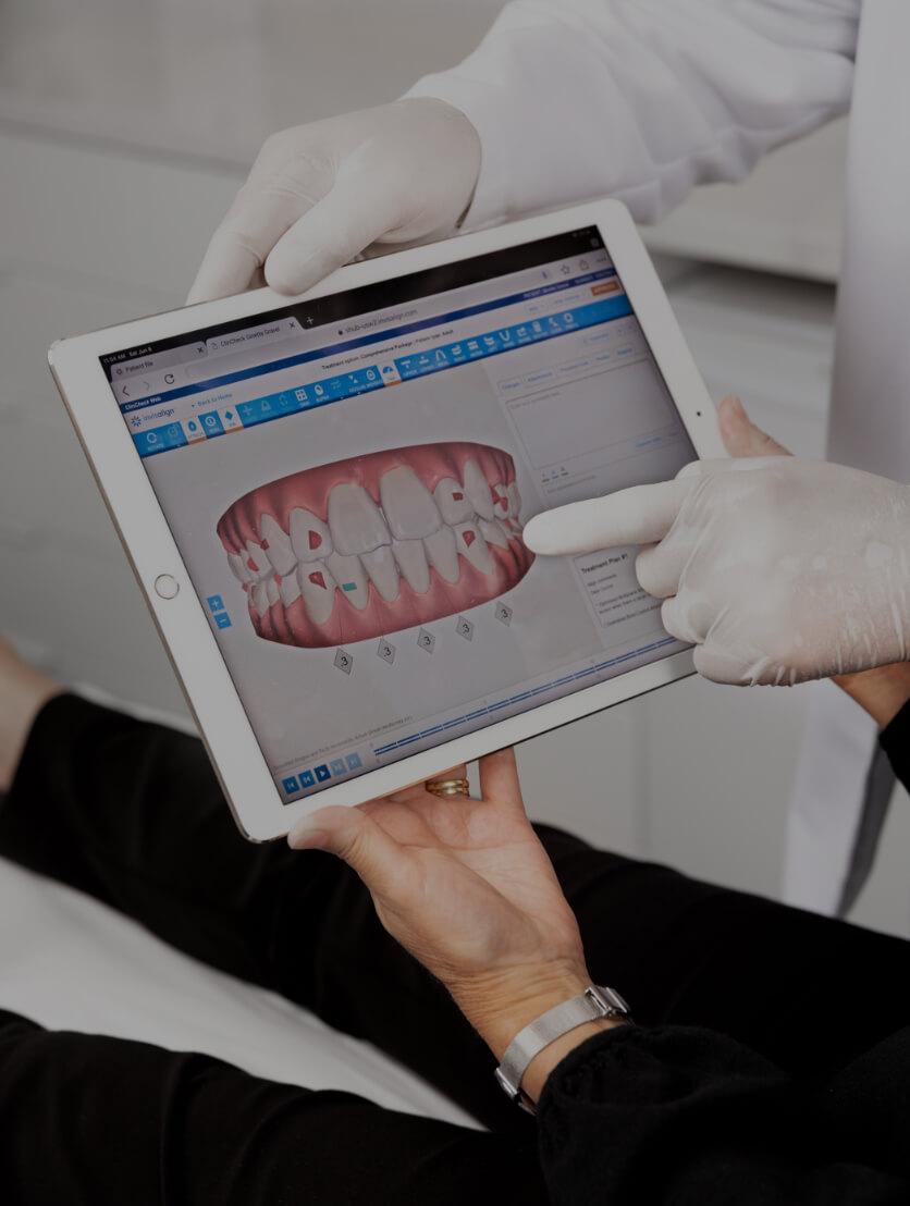 Le dentiste de la Clinique Chloé montrant une simulation Invisalign à sa patiente sur un iPad