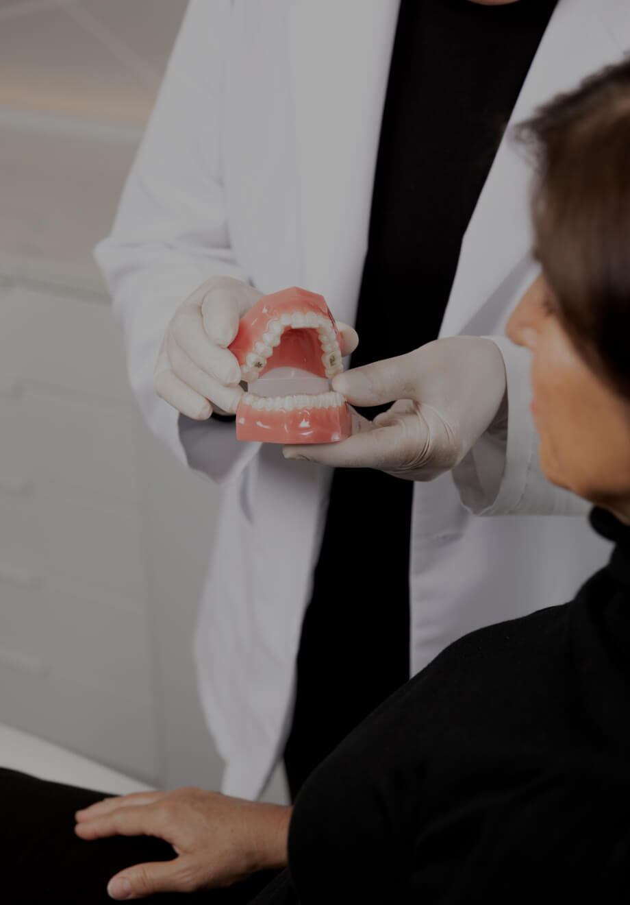 The dentist at Clinique Chloé holding dentures in his hands and explaining the Invisalign treatment to a female patient