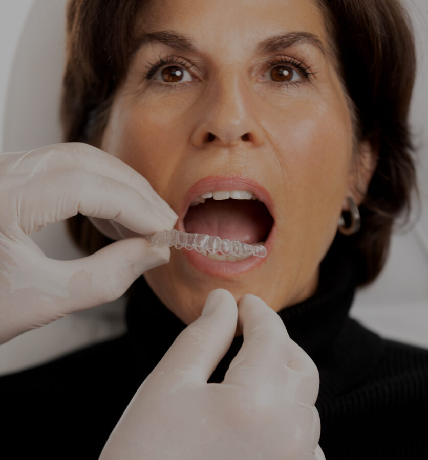 The dentist at Clinique Chloé installing an Invisalign clear aligner in a female patient's mouth