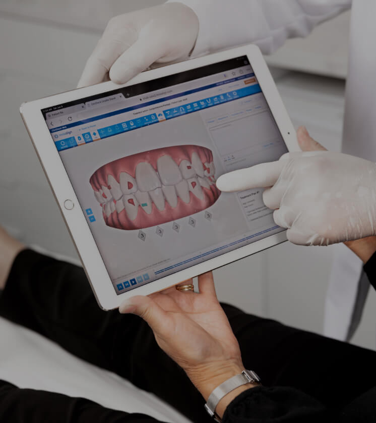 The dentist at Clinique Chloé showing an Invisalign simulation to his patient on an iPad