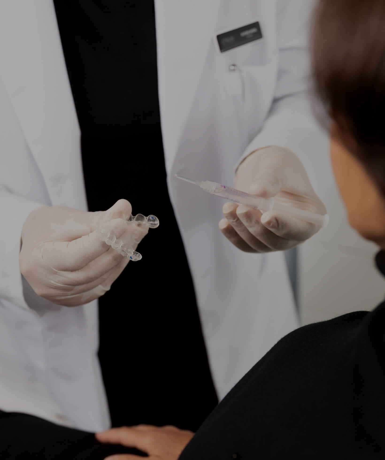 The dentist at Clinique Chloé explaining how teeth whitening works to a female patient