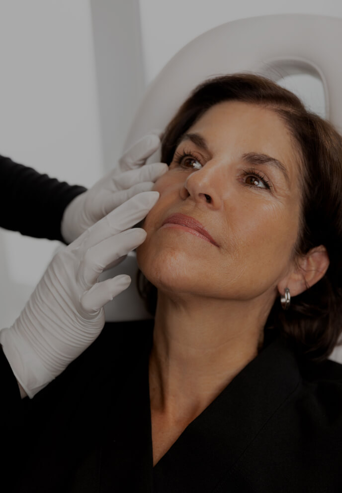 A medico-aesthetic technician from Clinique Chloé performing a visual examination of a patient's acne symptoms