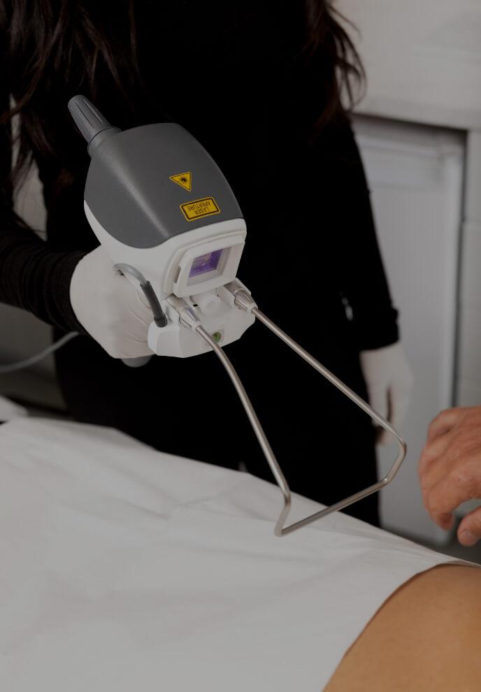 Une technicienne médico-esthétique de la Clinique Chloé tenant la pièce à main laser Hot Sculpting devant une patiente