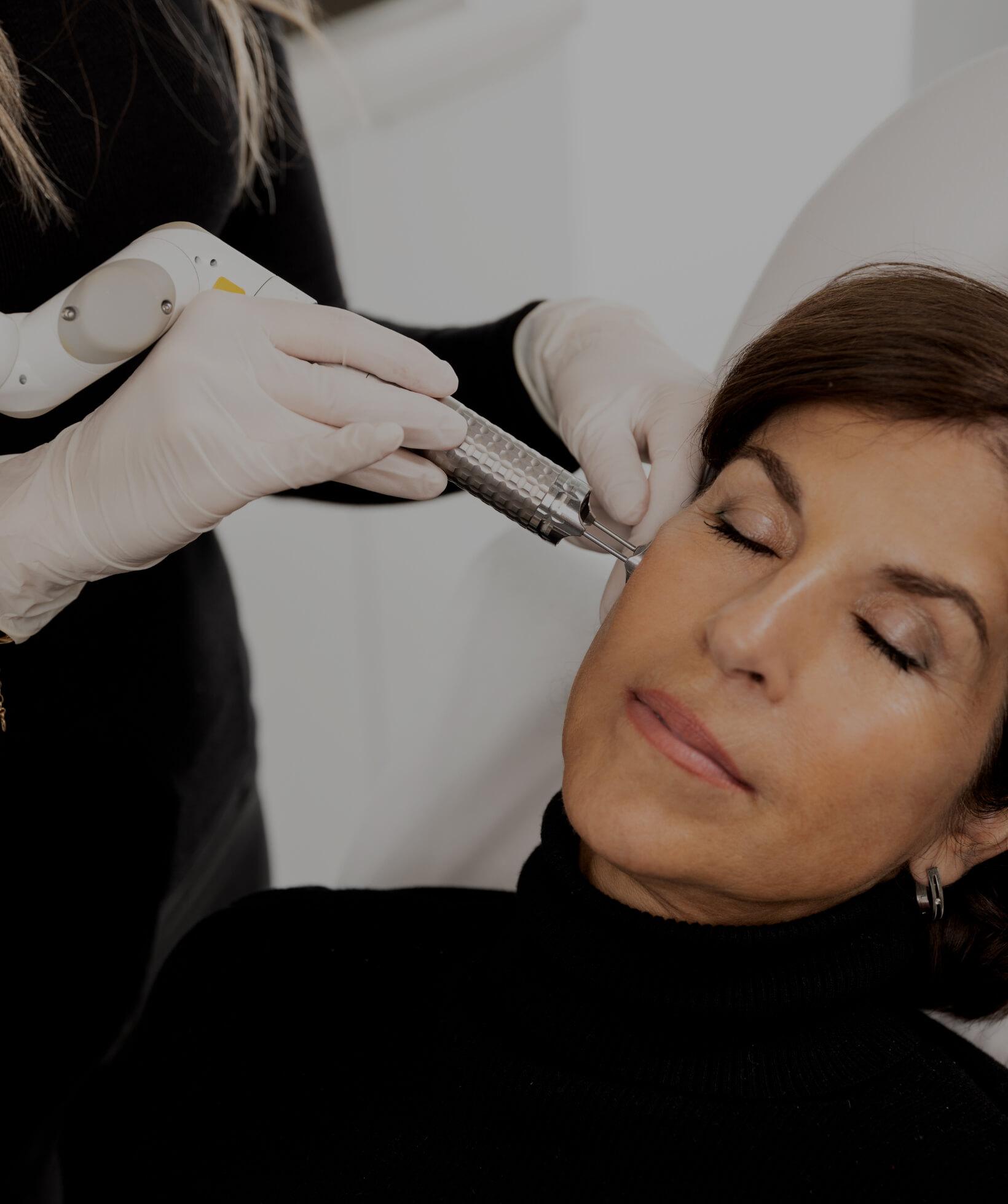 Une technicienne médico-esthétique de la Clinique Chloé traitant le visage d'une patiente avec le laser fractionné