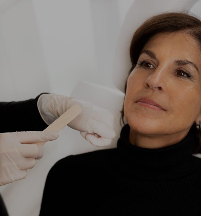 Une technicienne de la Clinique Chloé appliquant de la crème anesthésiante sur le visage d'une patiente avec un bâton de bois