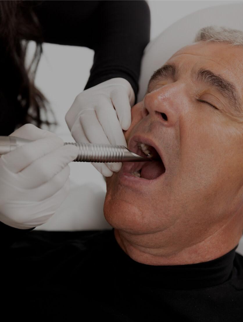 Une technicienne de la Clinique Chloé pratiquant un traitement laser intra-oral NightLase dans la bouche d'un patient