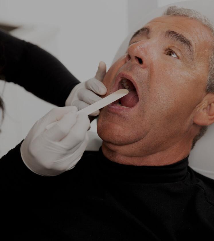 Une technicienne de la Clinique Chloé pratiquant un examen visuel de la gorge d'un patient avant son traitement NightLase