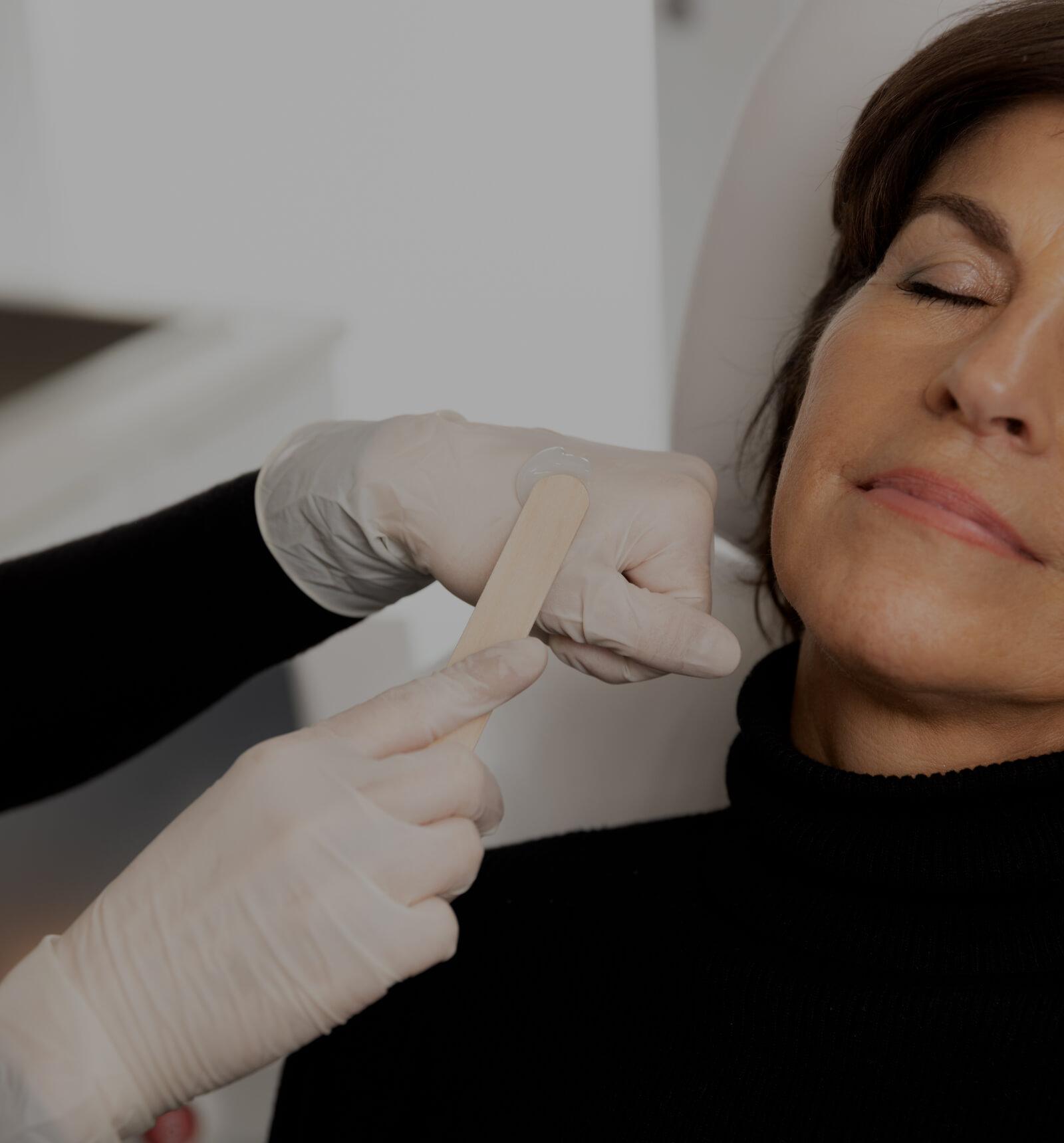 Une technicienne médico-esthétique de la Clinique Chloé appliquant du gel sur le visage d'une patiente