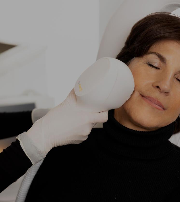 Une technicienne de la Clinique Chloé traitant le visage d'une patiente à l'aide d'un appareil de lumière intense pulsée