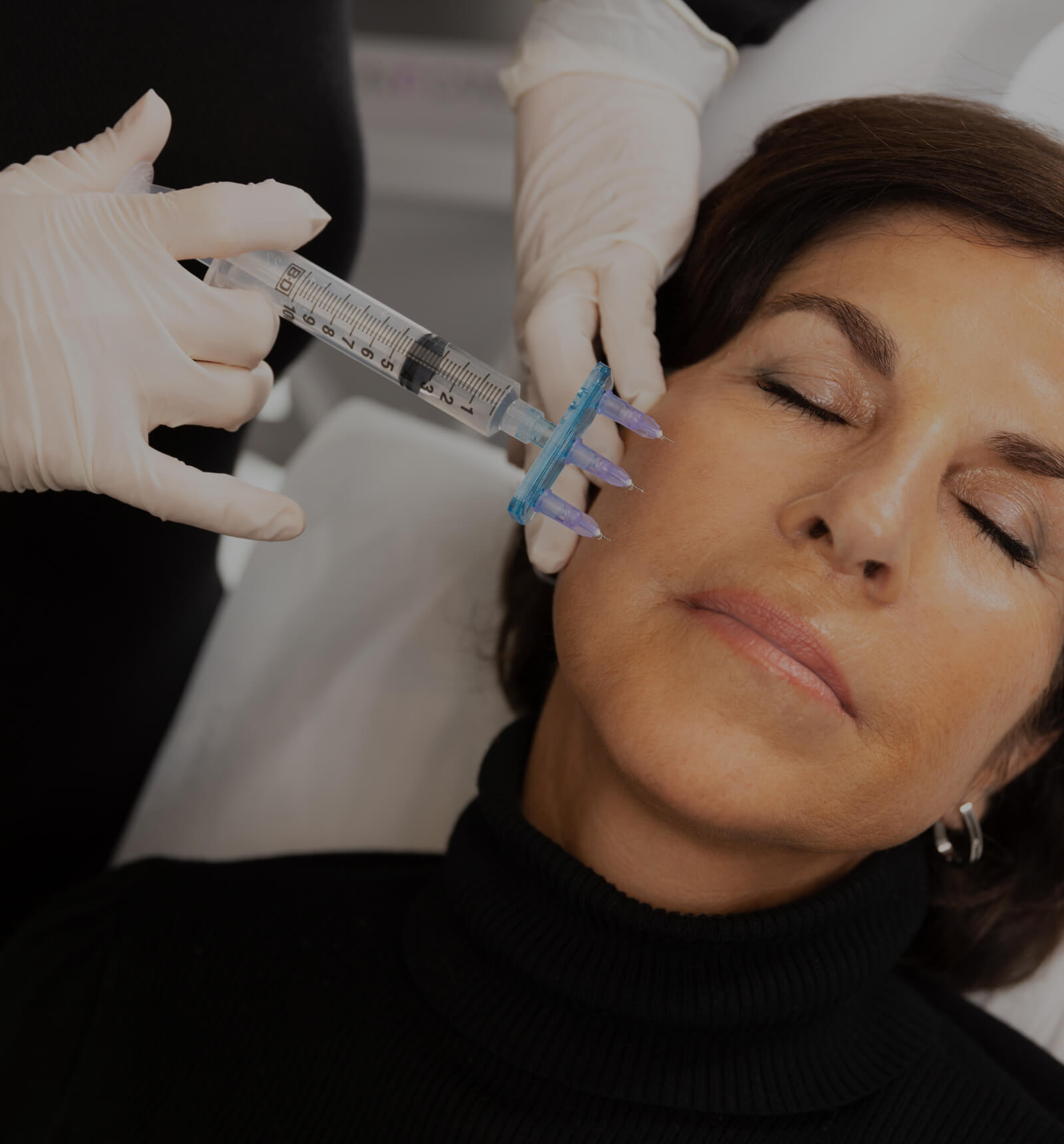 A nurse at Clinique Chloé performing local anesthesia on her patient's face using a multiport injector