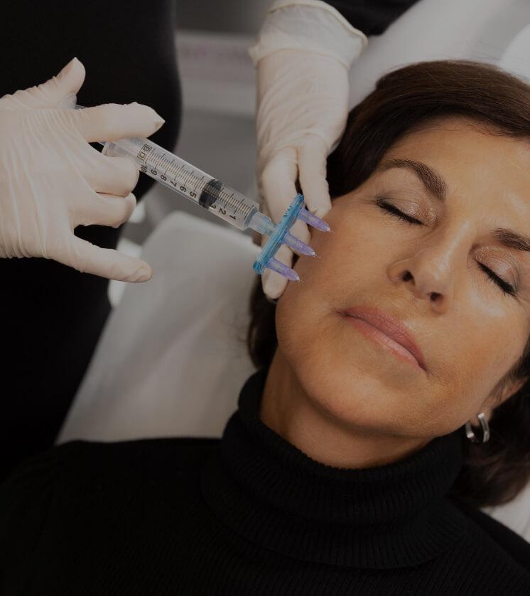 Une infirmière de la Clinique Chloé procédant à l'anesthésie locale du visage de sa patiente à l'aide d'une seringue