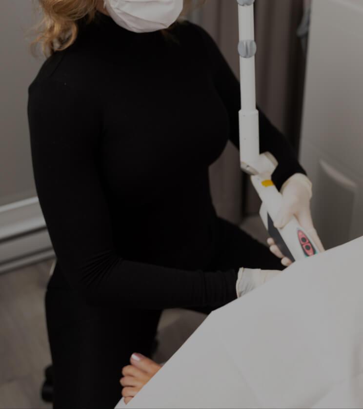 Une infirmière de la Clinique Chloé assise et insérant la pièce à main du laser RenovaLase dans le vagin d'une patiente