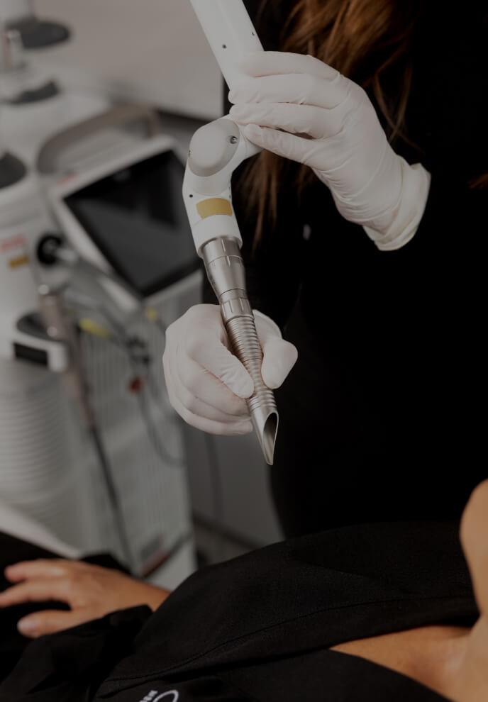 Une technicienne de la Clinique Chloé tenant la pièce à main du laser SmoothLiftin près de la bouche d'une patiente
