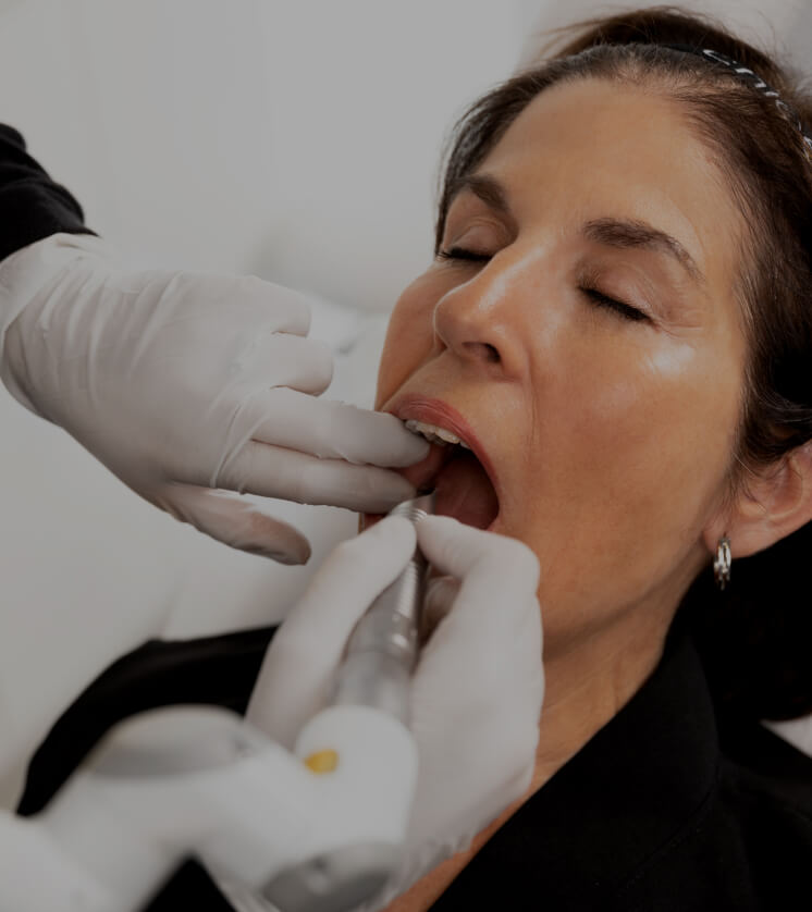 A medico-aesthetic technician at Clinique Chloé treating a female patient with the SmoothLiftin intraoral laser