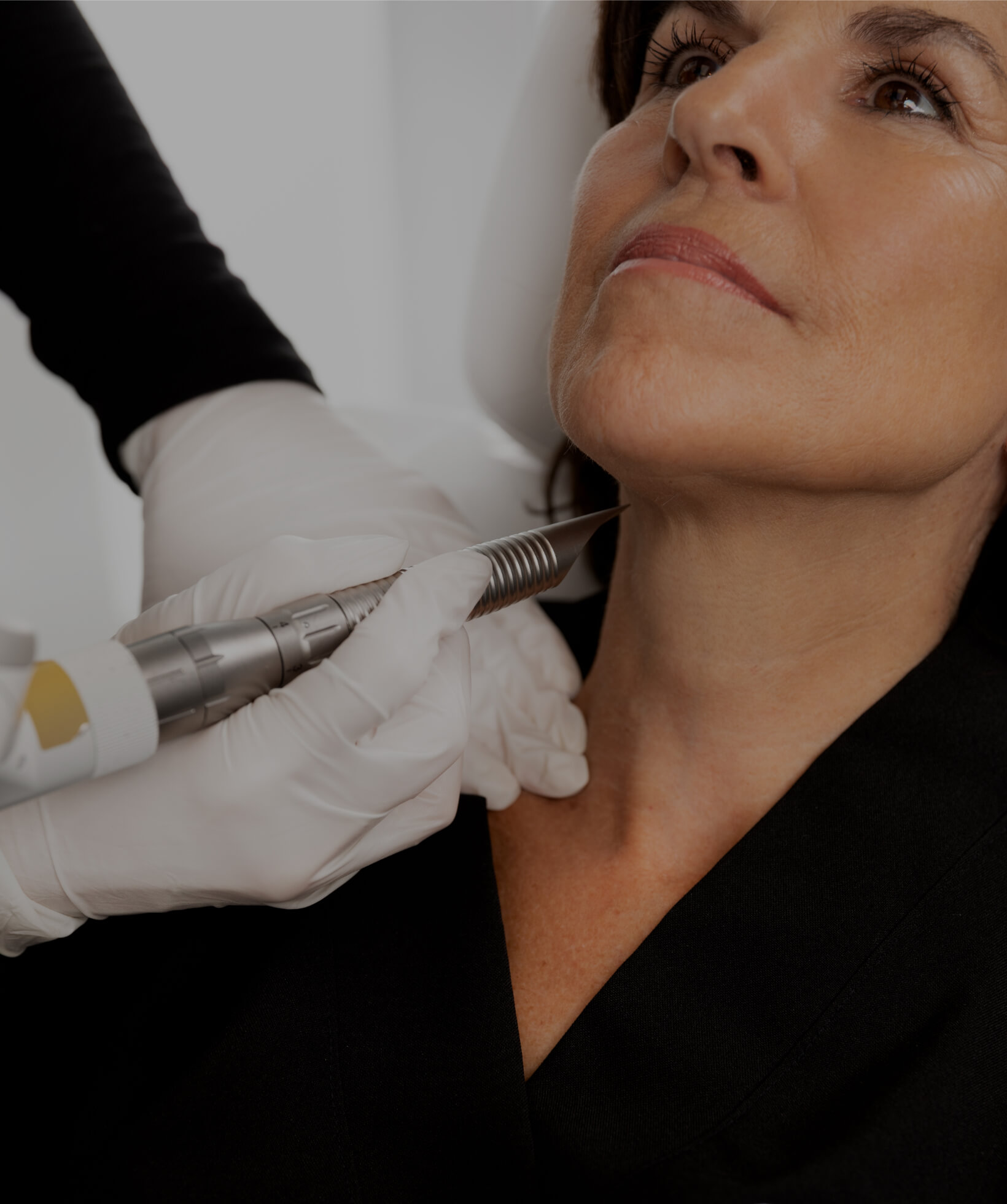 A medico-aesthetic technician from Clinique Chloé treating a patient's neck with the TightSculpting laser