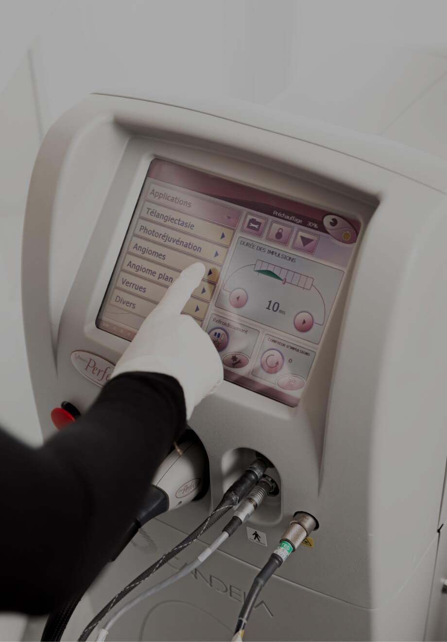 Une technicienne médico-esthétique de la Clinique Chloé ajustant des paramètres sur l'écran du laser Vbeam avec son doigt