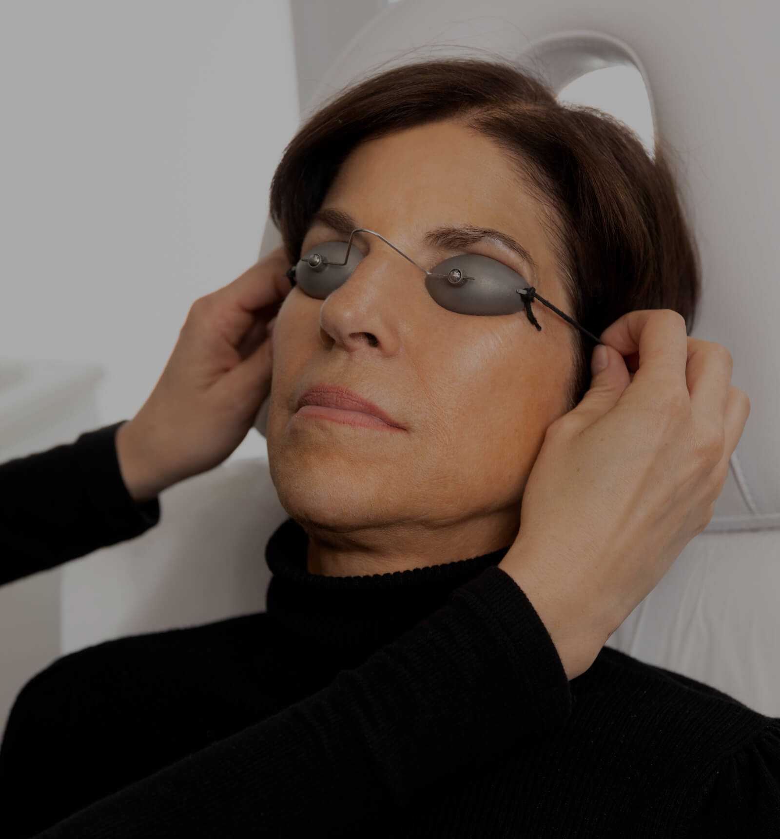 A medical aesthetic technician from Clinique Chloé installing laser protective glasses on a patient's eyes