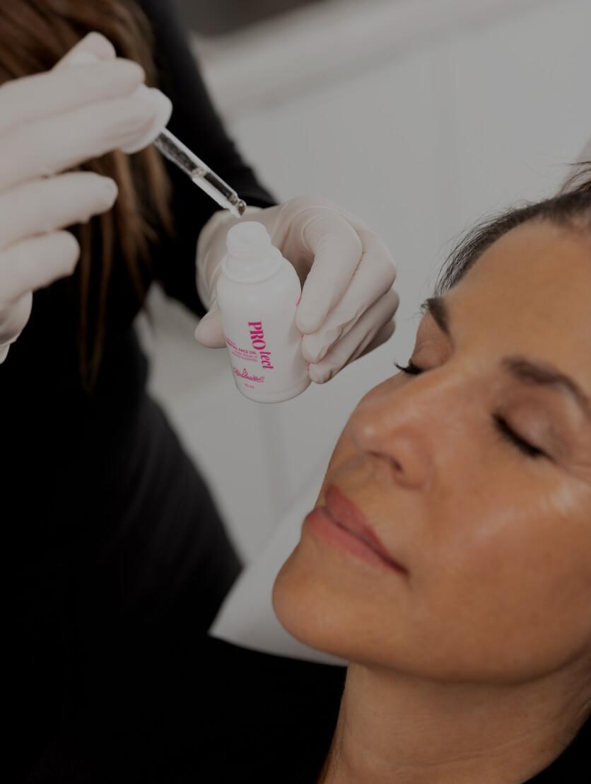 Une technicienne de la Clinique Chloé appliquant un sérum sur le visage d'une patiente après un traitement de microneedling