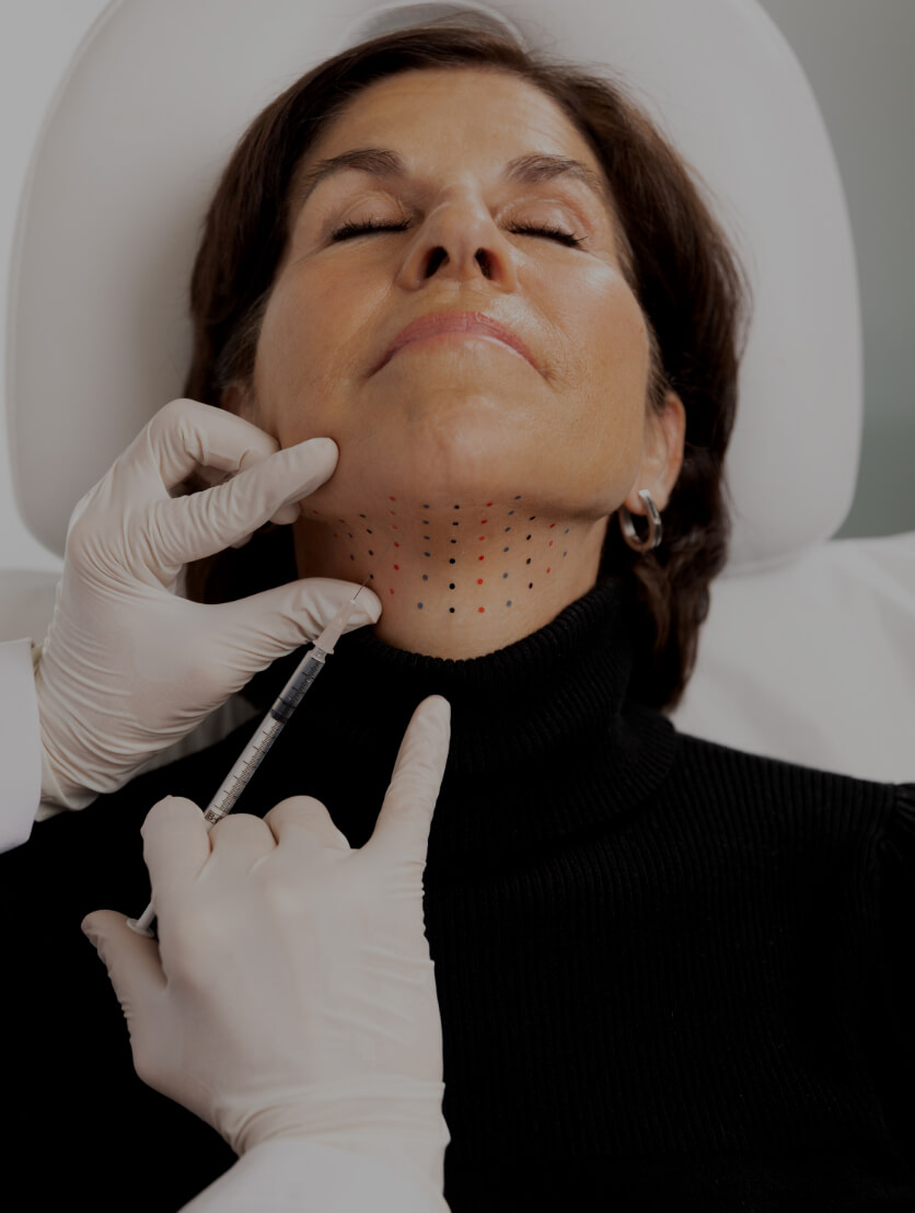 A doctor at Clinique Chloé doing Belkyra injections into a female patient's double chin