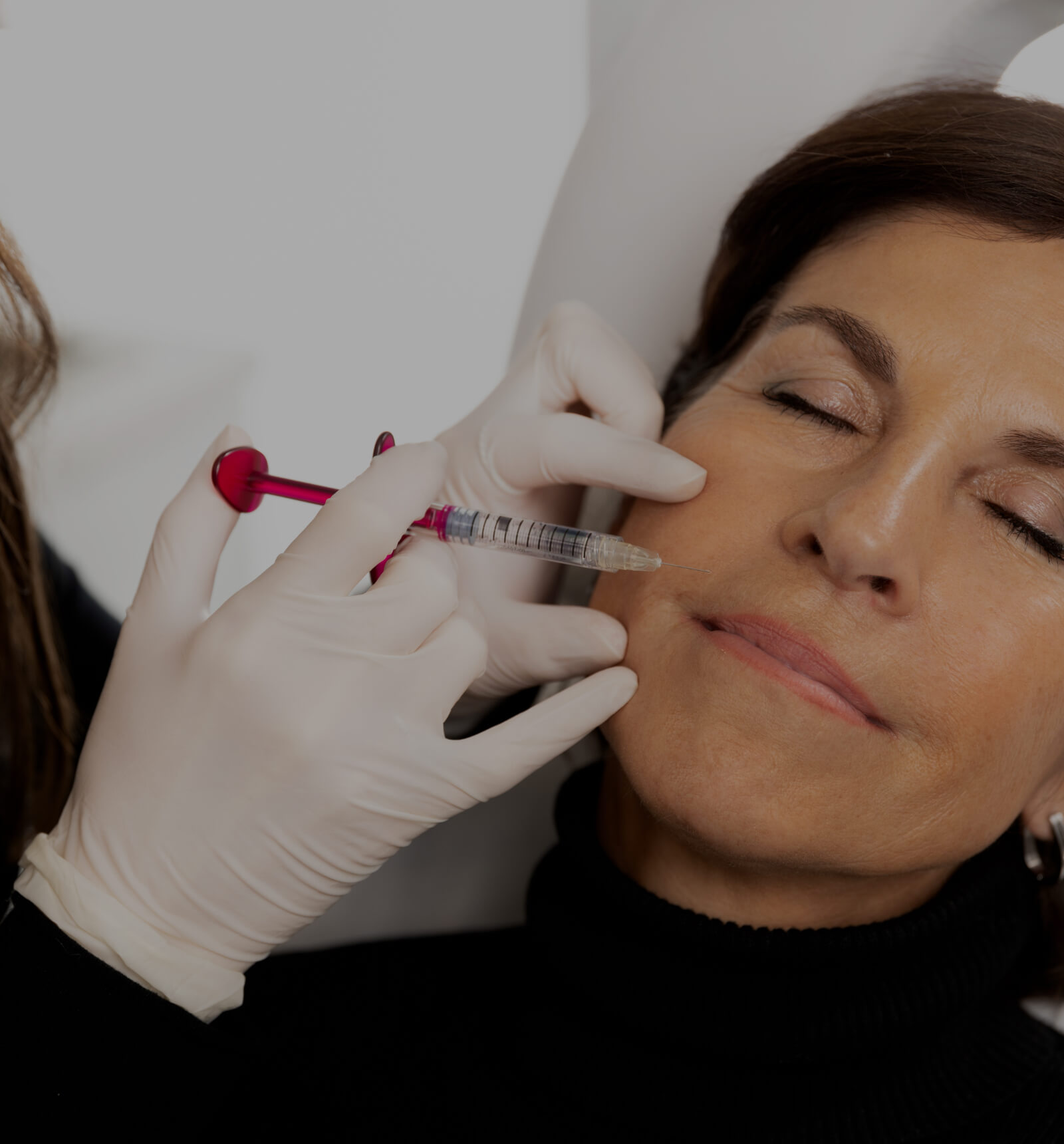 A doctor from Clinique Chloé performing a mesotherapy treatment on a female patient to reduce her nasolabial folds