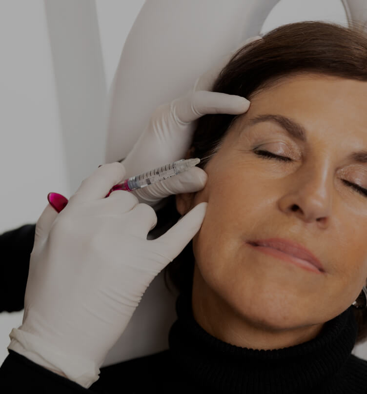 A doctor from Clinique Chloé performing a mesotherapy treatment on a patient's face