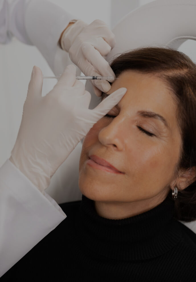A doctor from Clinique Chloé performing neuromodulator injections into a patient's forehead