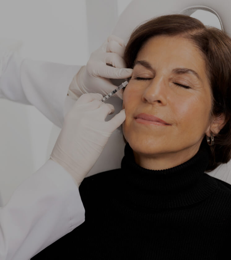 A doctor at Clinique Chloé treating a patient's crow's feet with neuromodulator injections like Botox